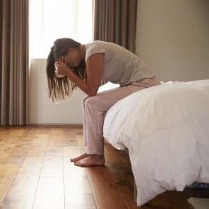 Woman Suffering From Depression Sitting On Bed And Crying - High Conflict Divorce Attorneys